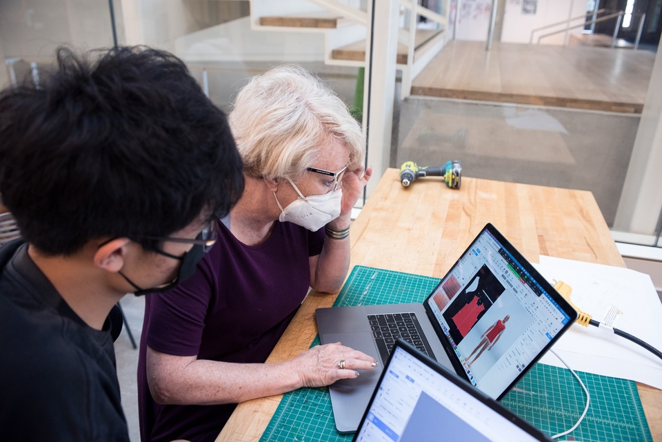 Instructor demonstrates a 3D clothing modeling software on a laptop to a student.