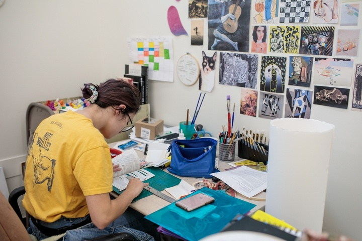Person works on a book-based project at their studio desk.
