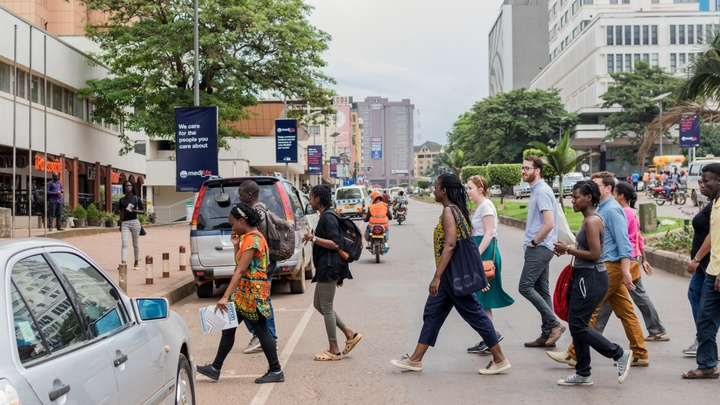 Group of people crossing a street in Kampala, Uganda. Multi-story apartment and office buildings can be seen down the road, and several people on mopeds ride by.
