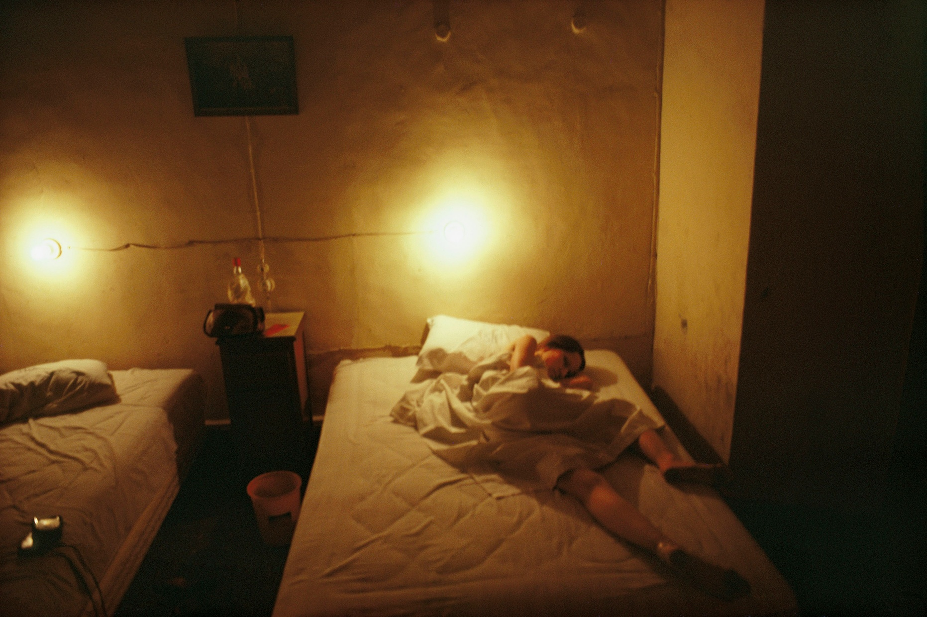 Color photograph of a girl curled up under a sheet on one of two beds in a spare and run down room where there is a bucket on the floor between the beds and bare light bulbs illuminating the space.