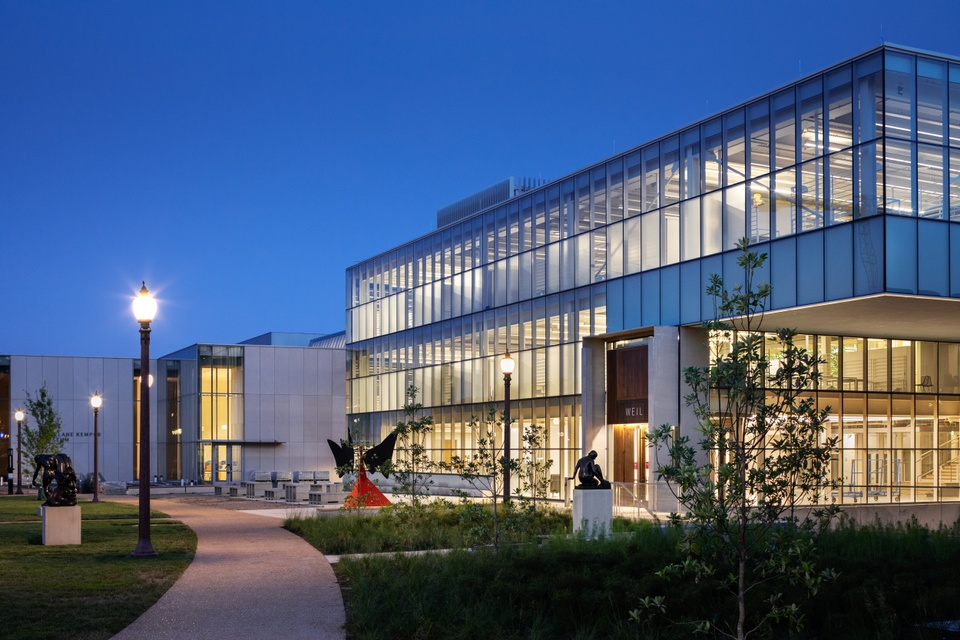 3-story glass walled building and a cantilever on one corner. Walkways wind by and a bright red Calder sculpture sits on the patio outside.