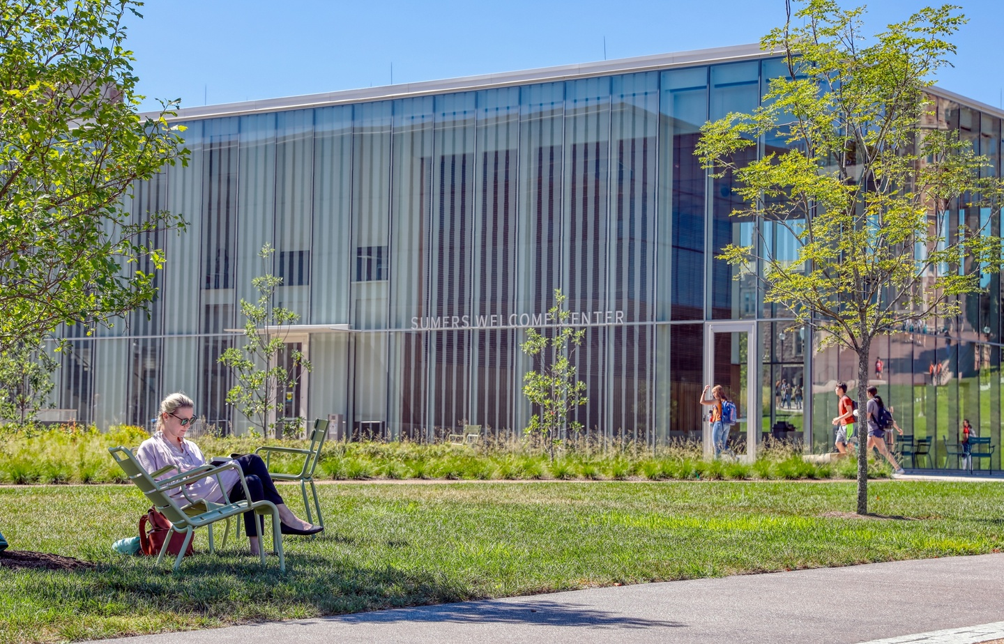 Person sits in a metal lawn chair in the shade of a little tree in front of a glass-walled building labeled Sumers Welcome Center.