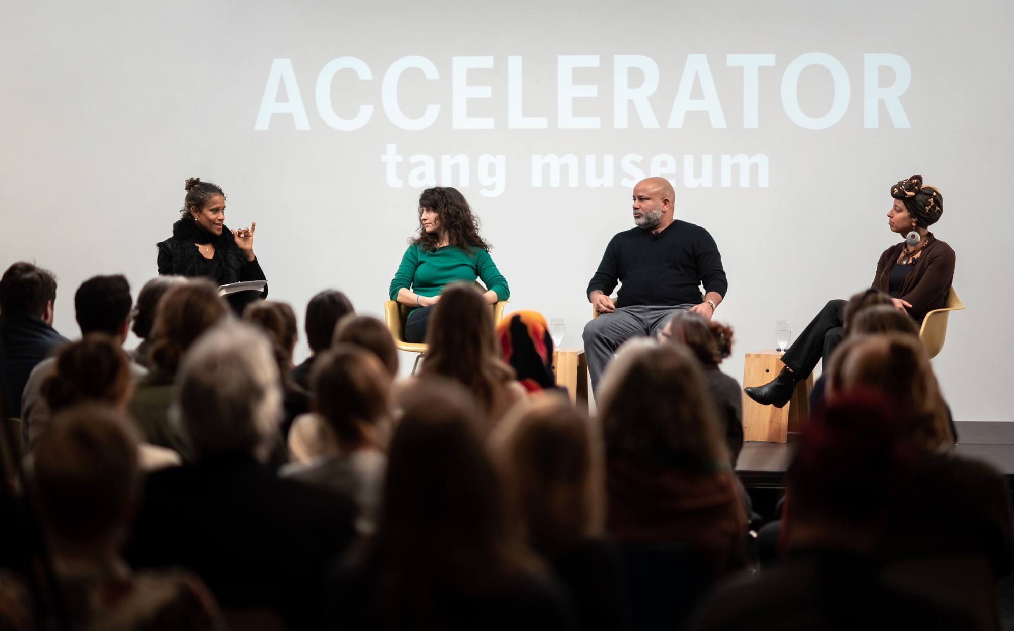"Four people, two black women, one black man, and one white woman, sit on a stage in front of a crowd with the words ""ACCELERATOR tang museum"" projected behind them."