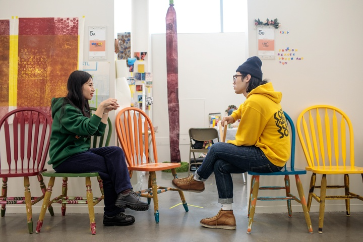 Two students sit on a row of colorfully painted kitchen chairs outside an artist's studio, discussing something animatedly.