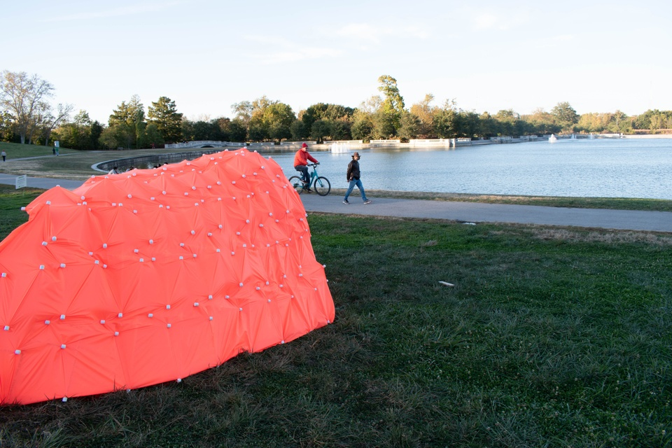 Pinkish-orange tent structure built on the grass in Forest Park, overlooking the water.