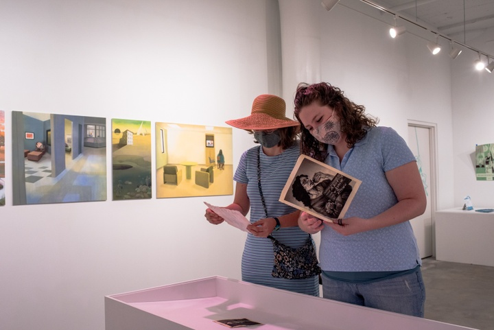 Two people looking at printed pieces from a display in a gallery space exhibiting illustration work.