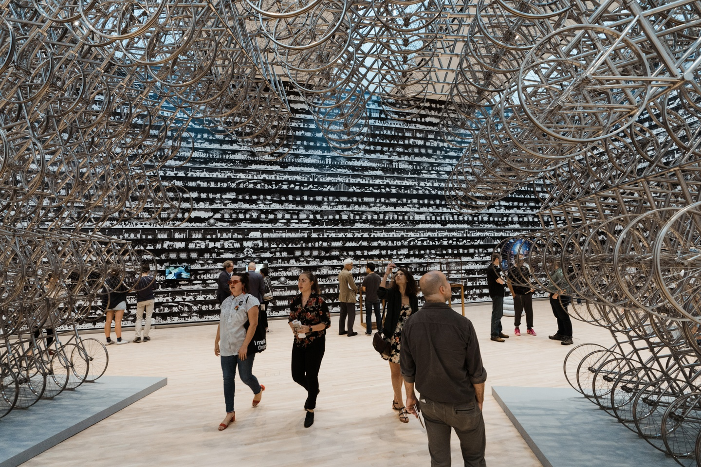 Installation of hundreds of silver bicycles, arranged in something of an arch pattern from ground to ceiling. Underneath people view the exhibition by Ai Weiwei; the back wall features a patterned black wallpaper and a couple of video monitors.