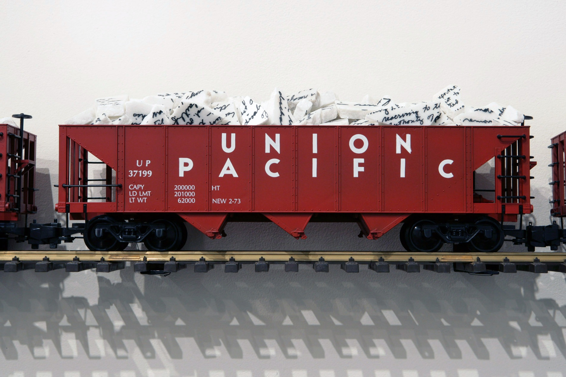 "A red toy train with ""Union Pacific"" in white letters on the side rests on a small train track attached to a wall. The train has pieces of broken, white marble in it."