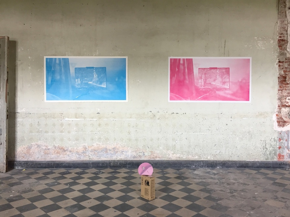 Two monochromatic silkscreen prints in blue and pink on an old wall