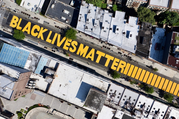 Aerial photo of a mural painted on the street, with the words Black Lives Matter in bold, all-caps yellow.