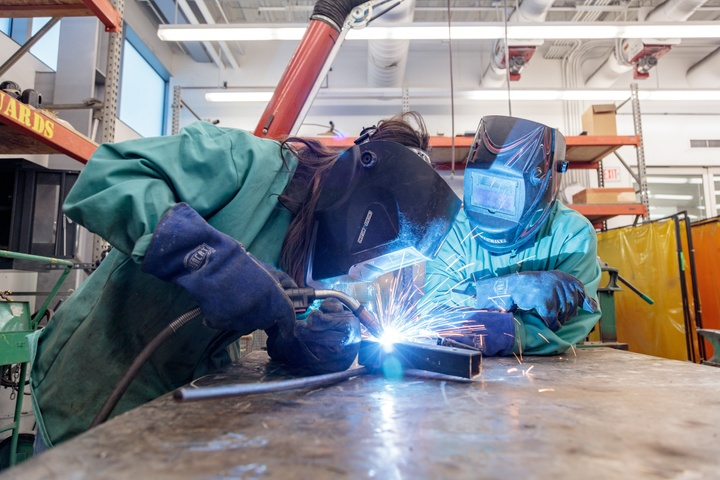 Two people use a welder in a metalworking shop.