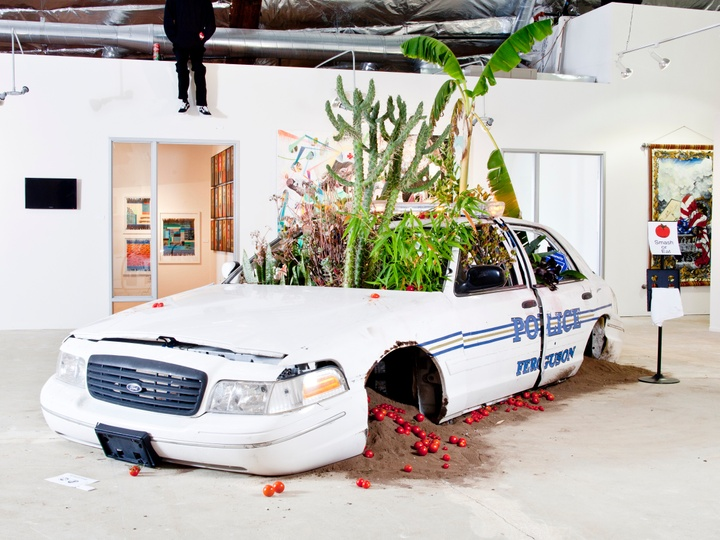 """A broken police car sits in the middle of a room. Plants grow out of its windshield, and tomatoes and sand spill out of the wheel wells.  Jordan Weber, """"American Dreamers Phase 2,"""" 2014-15. Installation view. (Photo courtesy of the artist)"""