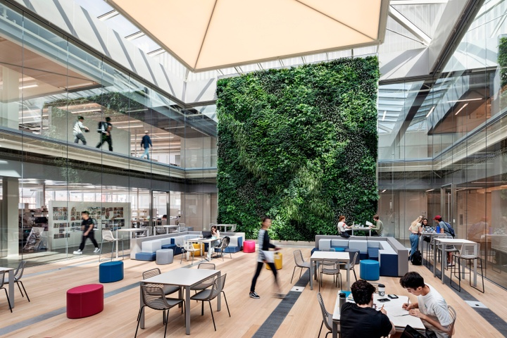 Light-filled interior atrium space with multiple tables and blue and pink soft seating, with people working in the space. The back wall features a floor-to-ceiling wall of green plants; the sides of the two-level space feature floor-to-ceiling glass, looking out into surrounding studio spaces.