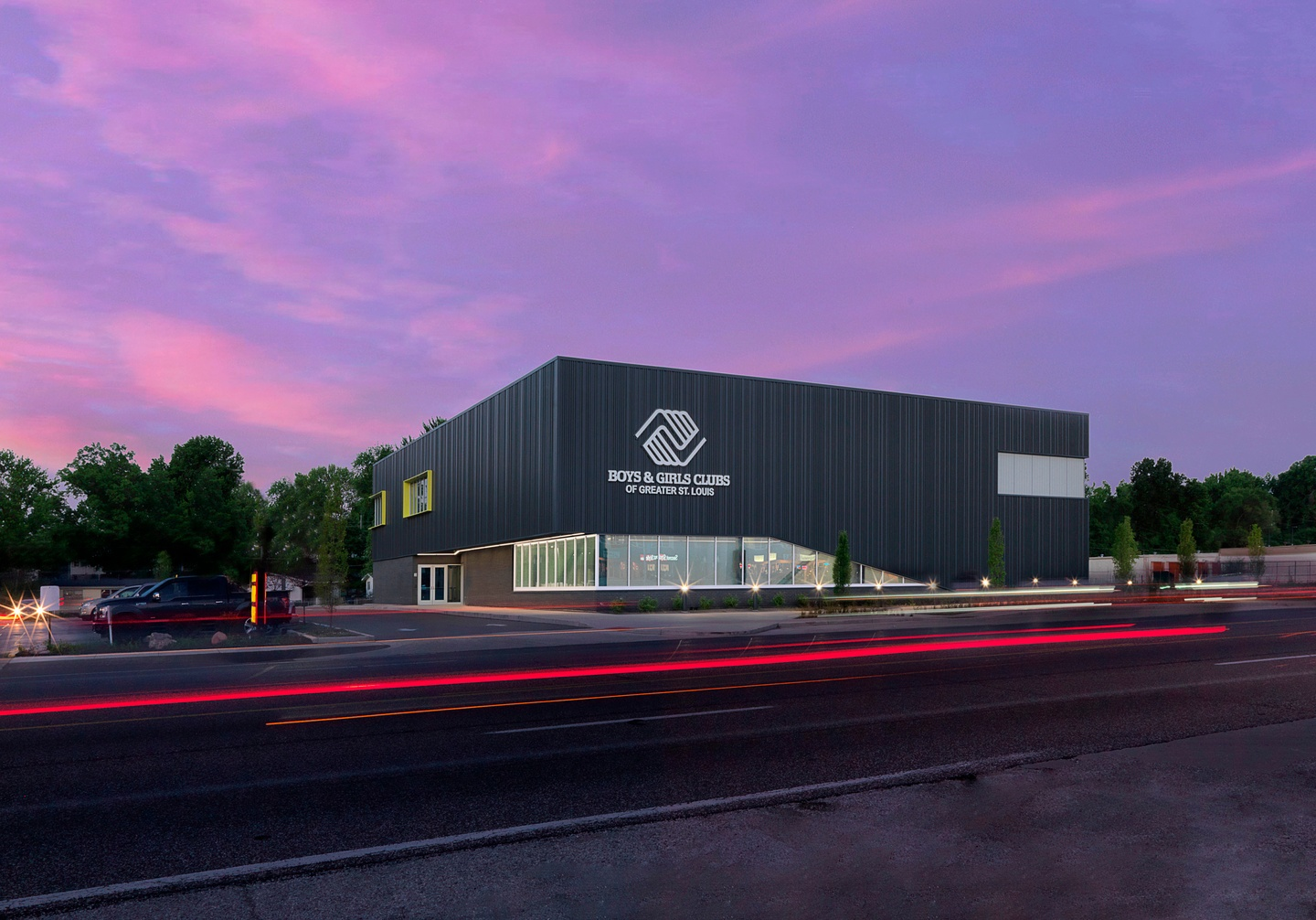 Photo of the exterior facade of new Boys & Girls club building, with a contemporary design including a bank of floor-to-ceiling first floor windows wrapping around the front corner of the building. The photo is shot at dusk with a purple sky and the street in front in view.