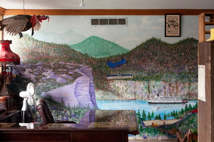 """Office with a marble-topped desk, leather office chair, fan, fringed lamp, and taxidermied turkey. The back wall is painted with a mural of midwest landscape. A riverboat floats down the river and a military helicopter flies overhead with a banner advertising """"Big Bags USA."""""""