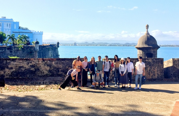 Group of people pose next to an old stone wall built around a city on the waterfront. There are palm trees and a bright blue castle-like structure on another peninsula behind them.