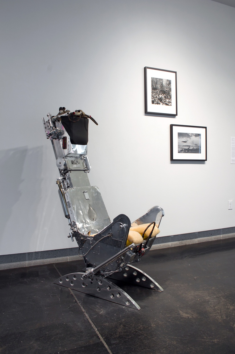 A metal, old-fashioned dentist's chair in a gallery with two framed photographs on the wall next to it.