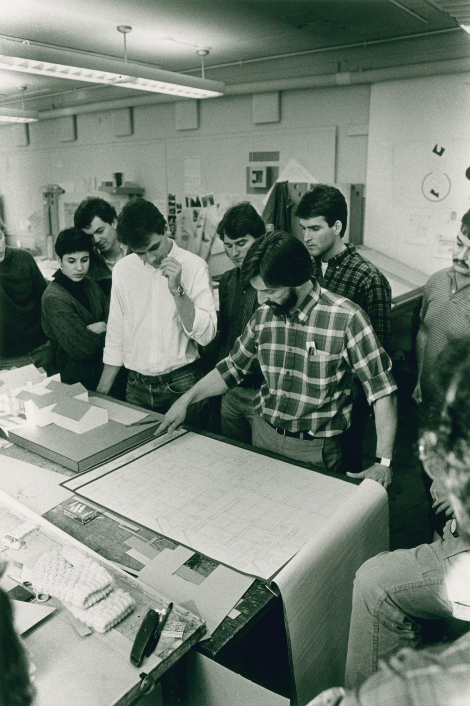 Black and white photo of a person gesturing to a blueprint document on a studio table while others look on.