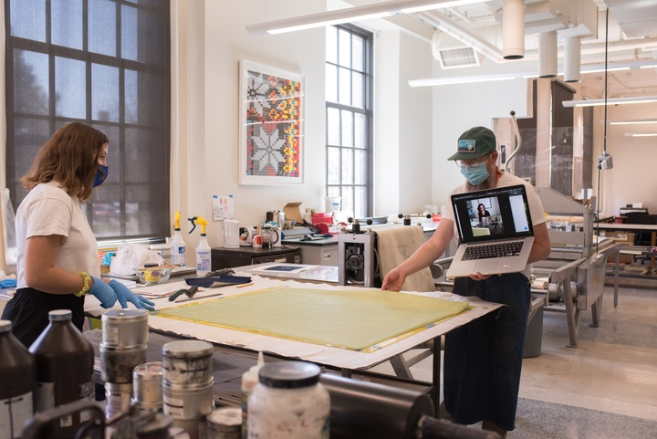 Person holds a laptop with video chat up to view a large cyanotype print on the table of a printmaking studio.
