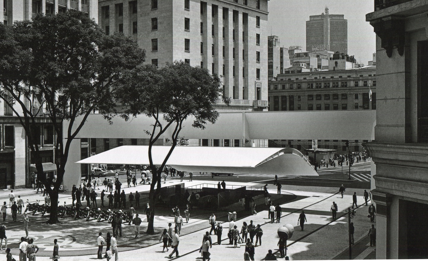 Black-and-white photo of people in a spacious city plaza, with a couple of tall trees and a canopy overhang