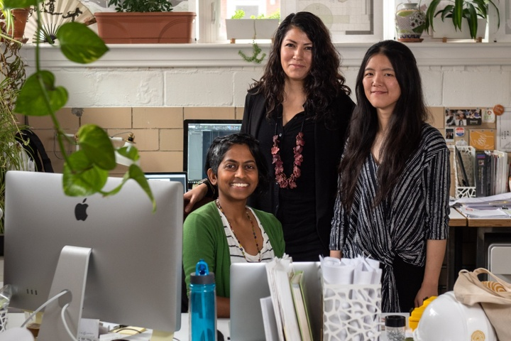 Three people posing for a photo at a desk in an office space filled with plants.