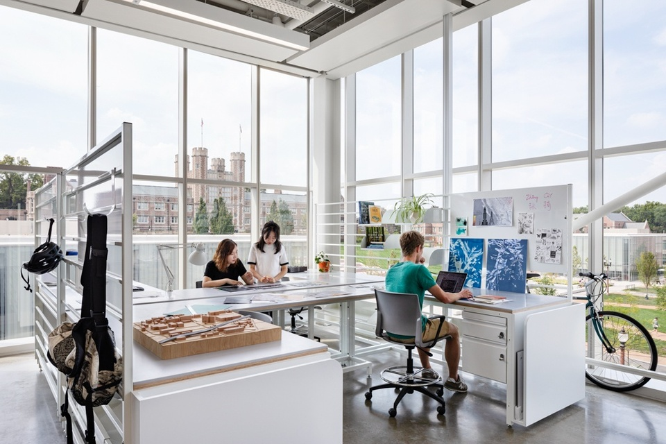Corner of studio space with several L-shaped desks, floor to ceiling windows, and a view of Brookings Hall.
