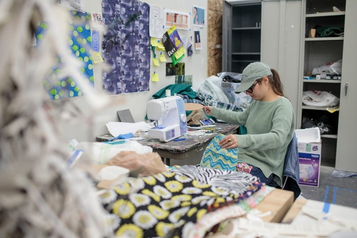 Person works on a fabric project at an L shaped desk covered in fabric scraps and a sewing machine.