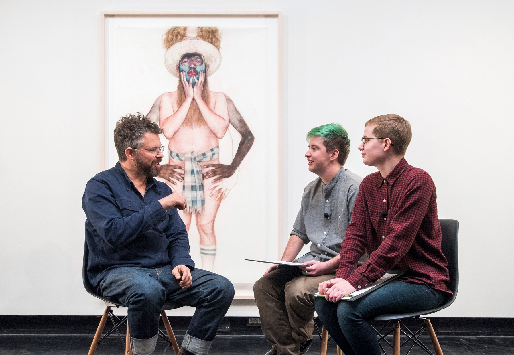 Artist Geoffrey Chadsey, a light-skinned, male, sits on a chair across from two light-skinned students, also sitting in chairs. A large framed artwork hangs on a wall behind them.