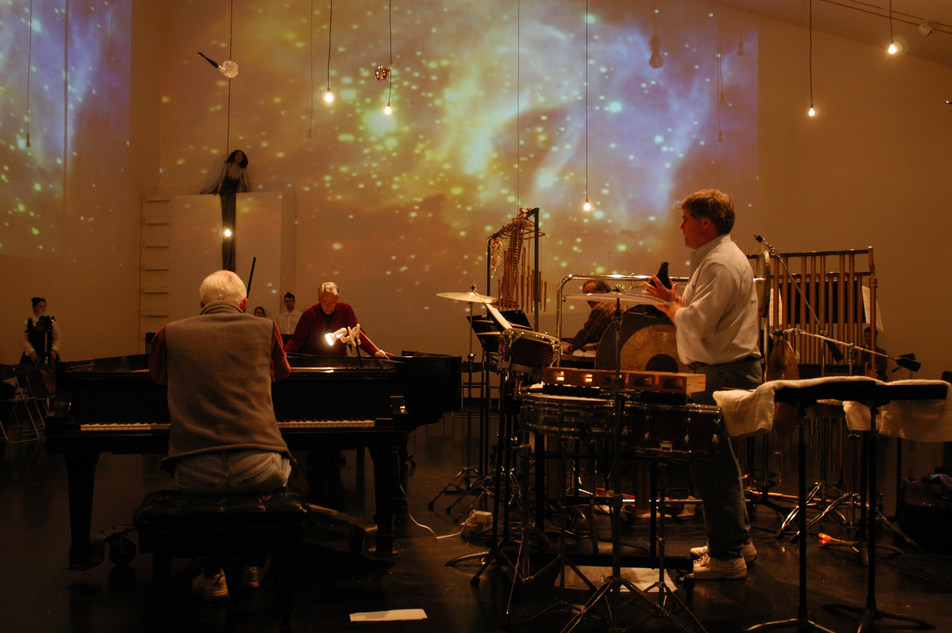 A group of musicians perform in a large, open space with images of stars and galaxies projected on the walls around them.