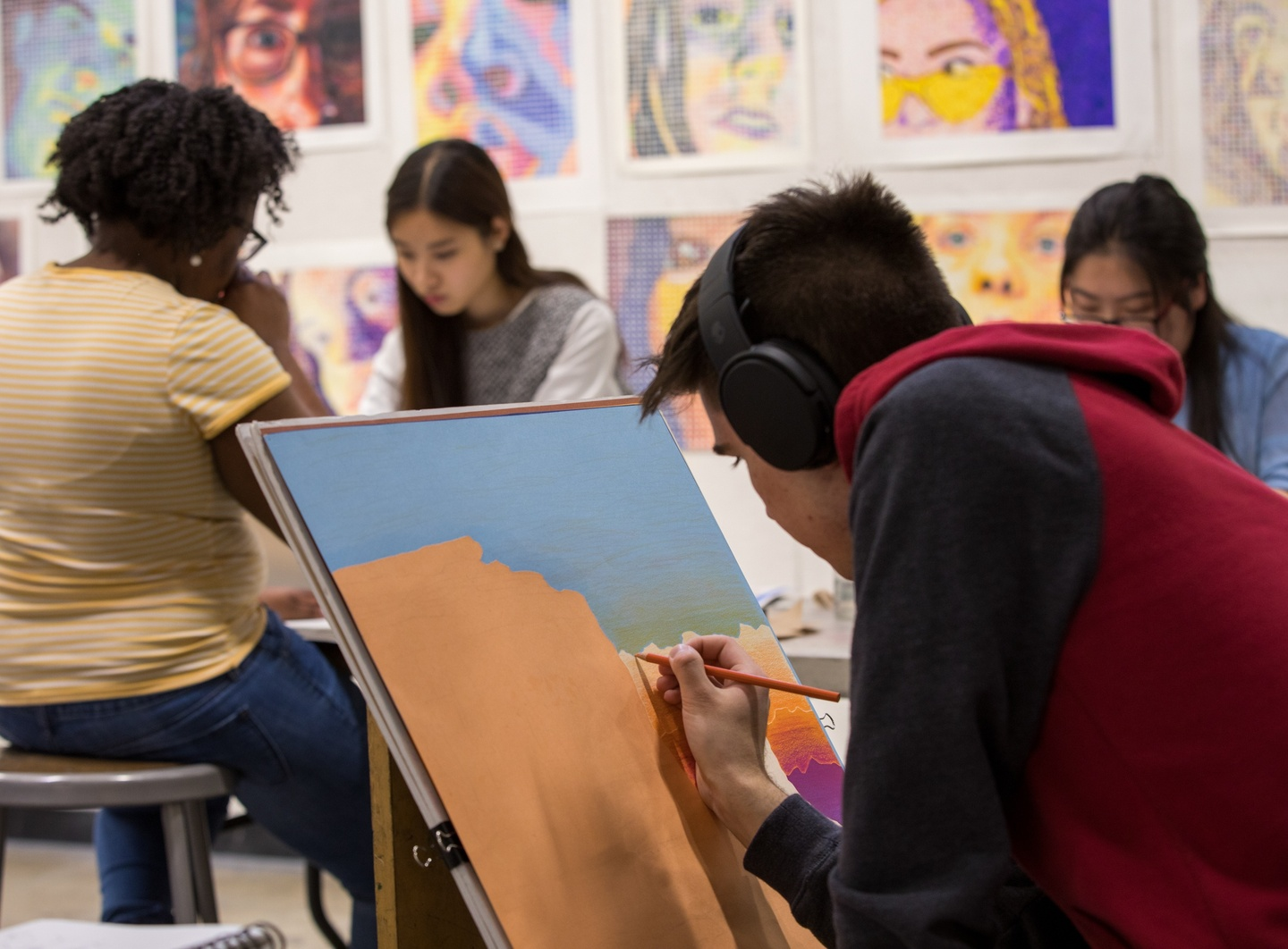 Person in headphones bends over a painting of a desert landscape. Several other people work in the background. The wall is hung with colorful portrait drawings.