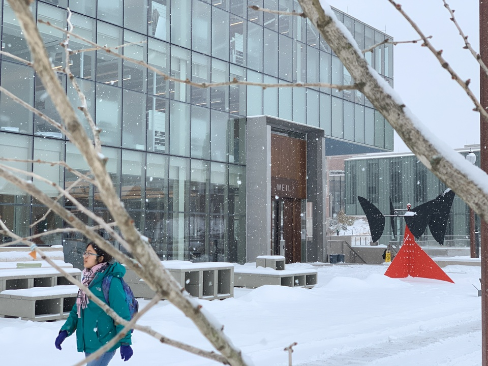 A student walks through snow drifts outside Weil Hall. The bright red Calder sculpture stands out against the snow.