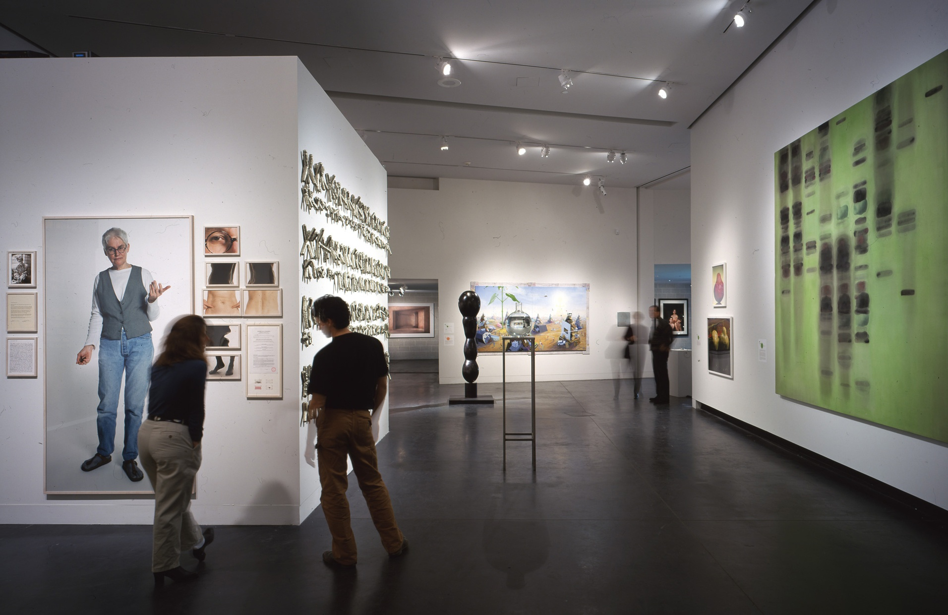 Two blurred people stand reading a wall label in a gallery next to numerous images of different sections of a human body.