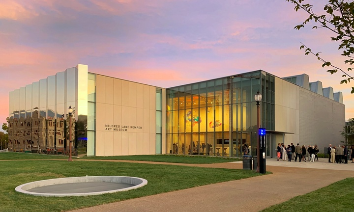 Kemper Art Museum backed by a pink and purple sunset. The interior is lit and a Tomas Saraceno sculpture can be seen suspended from the ceiling of the lobby.