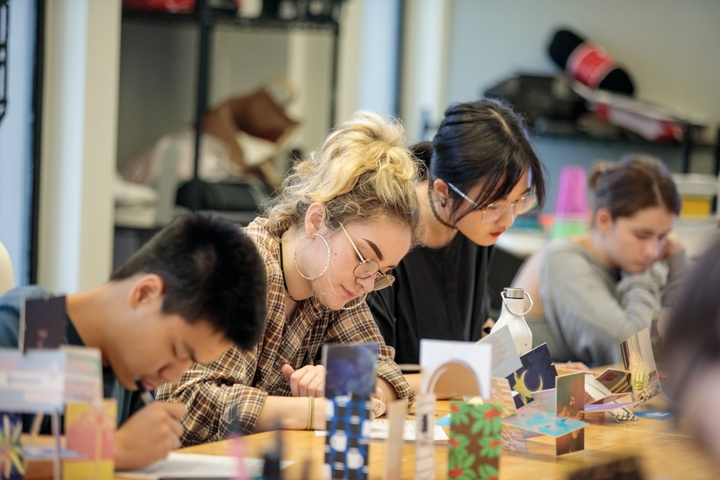 Several people sitting at a table write in notebooks. A row of models built from patterned cardstock sit in front of them.