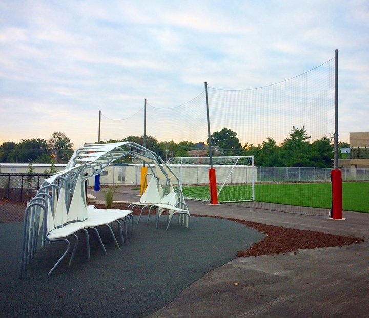 White seating and shade structure next to a soccer field.