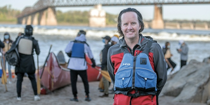 Faculty member Derek Hoeferlin stands, with a life jacket on, in the foreground, with his students preparing to canoe behind him. The river and a bridge are in the background.
