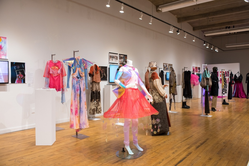 Gallery space full of mannequins and racks exhibiting fashion design garments.