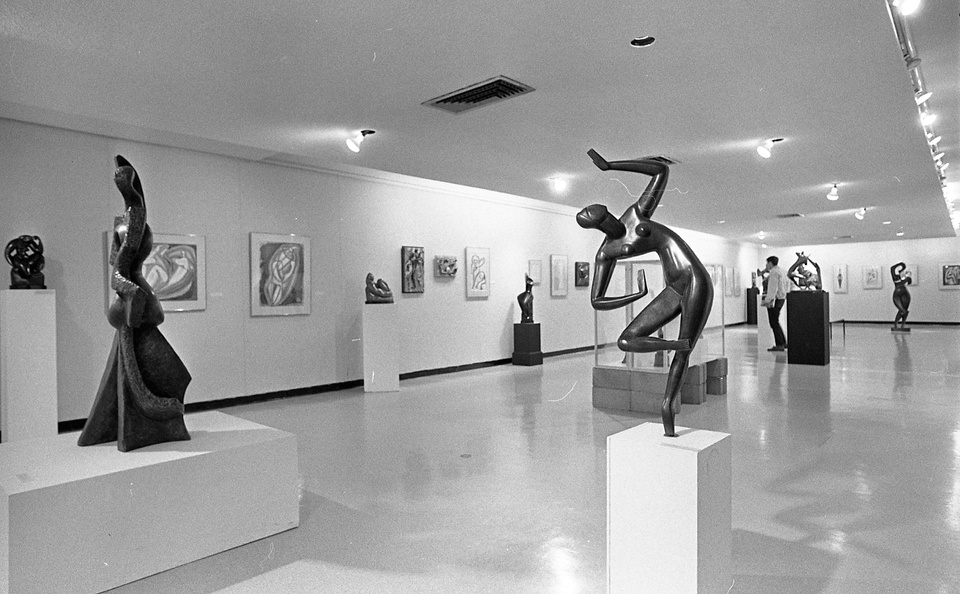 Gallery space with modern art sculptures and abstract paintings.