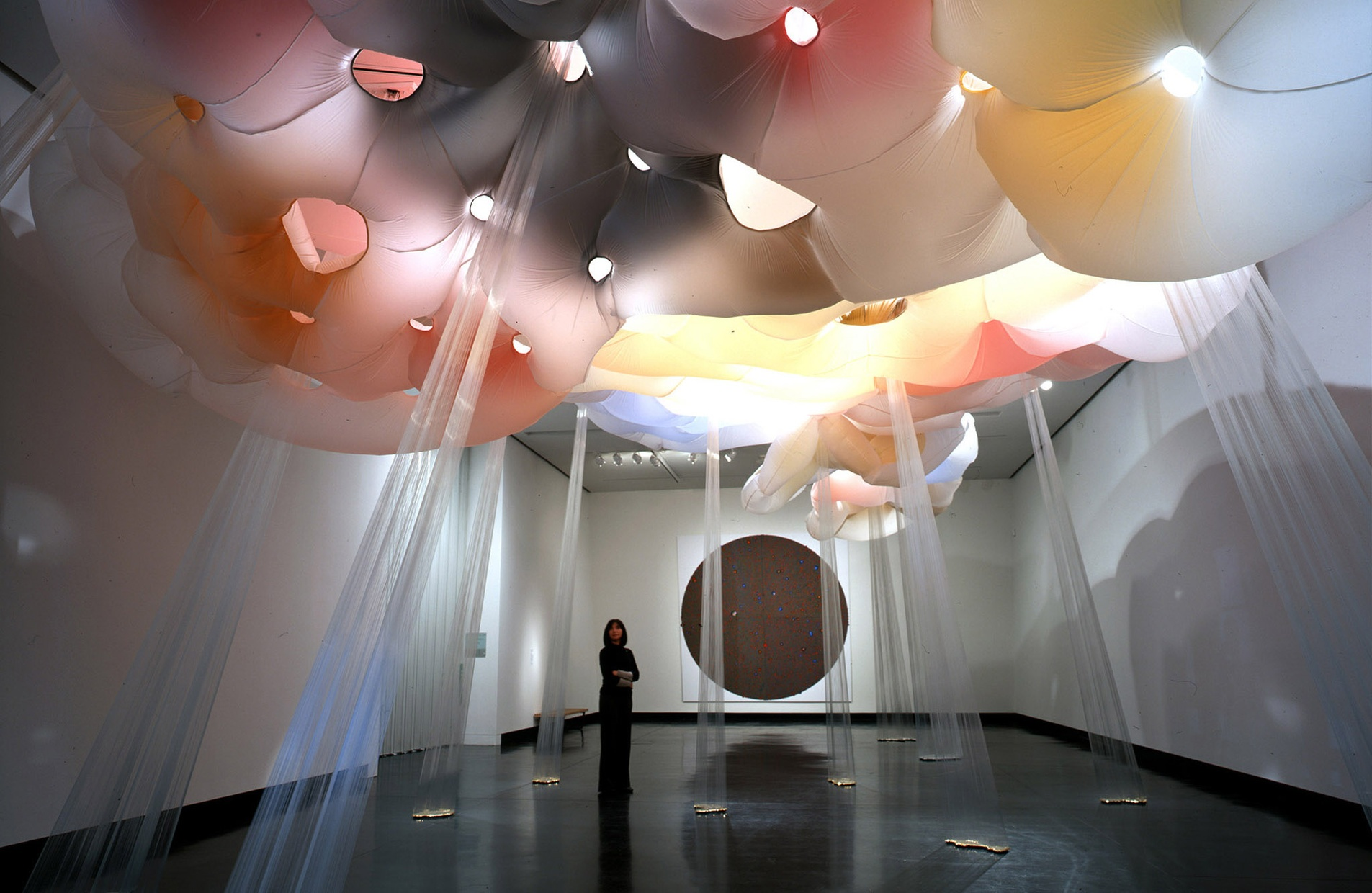 A woman stands in a gallery looking up at a red, yellow, black, and white cloud-like sculpture on the ceiling with rays extending to the floor.