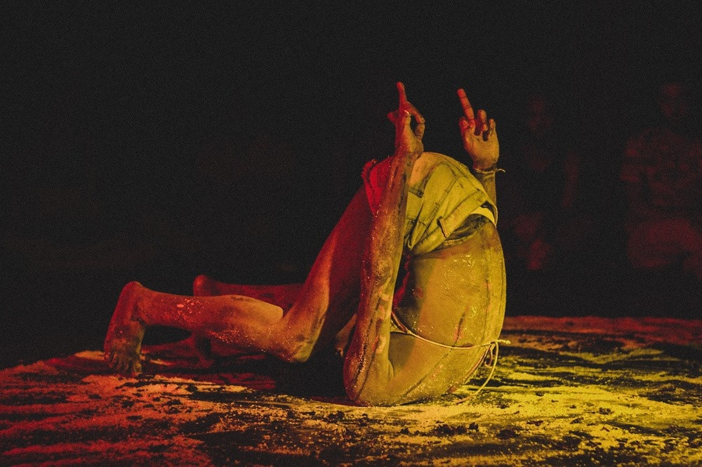 A person wearing a bikini top and short jeans is contorted, touching the floor only with the back of the head and the tip of the feet. The person's butt is pointing upward, as are the two arms that vertically lift middle fingers. The marks on the white powder over the dark floor seem to keep traces of intense movement. The person is bathed in red and yellow lights