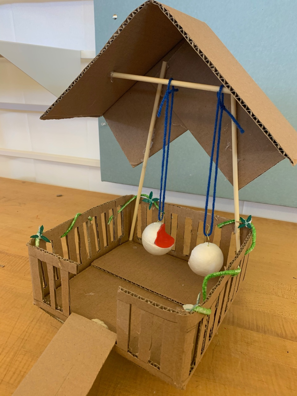 A model made out of cardboard, yarn, and other materials.