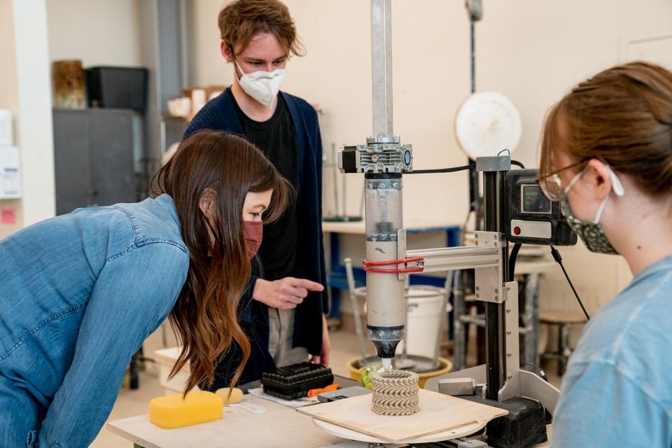 Three people watch a ceramics 3D printer construct a small vase.