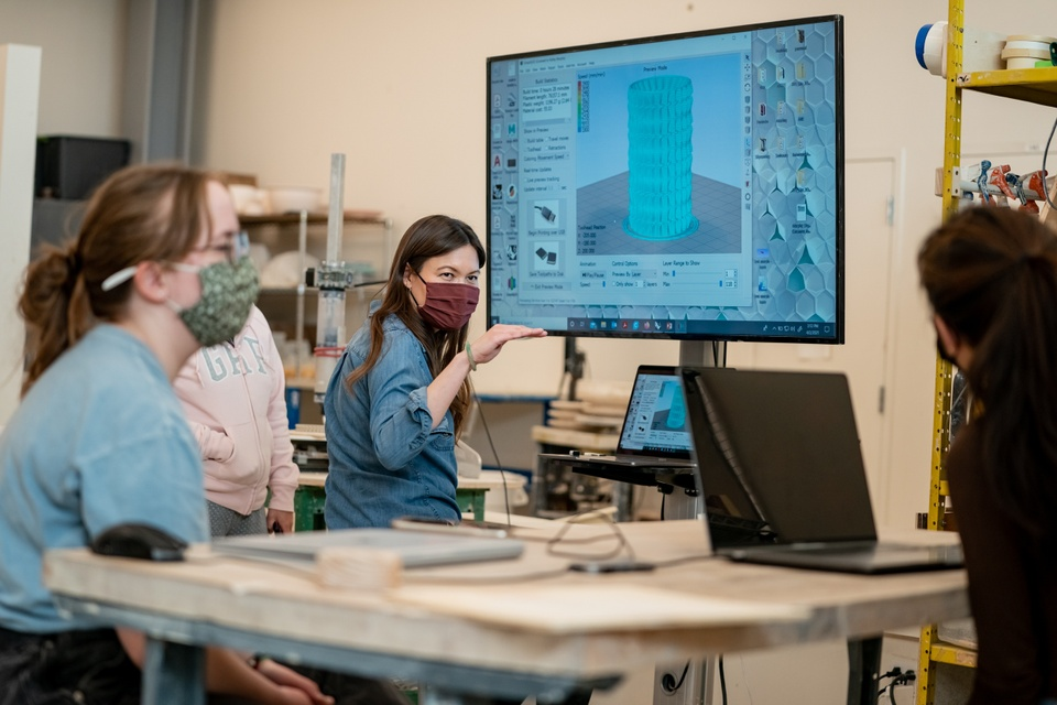 Instructor demonstrates 3D modeling software on a large screen to a group of people with laptops.