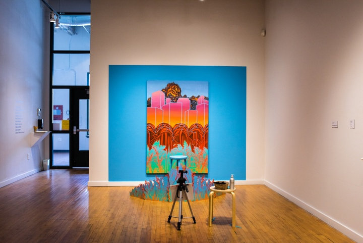 Gallery space with a large, colorful backdrop painting on one wall, fronted by a teal stool and an empty camera tripod facing the backdrop.