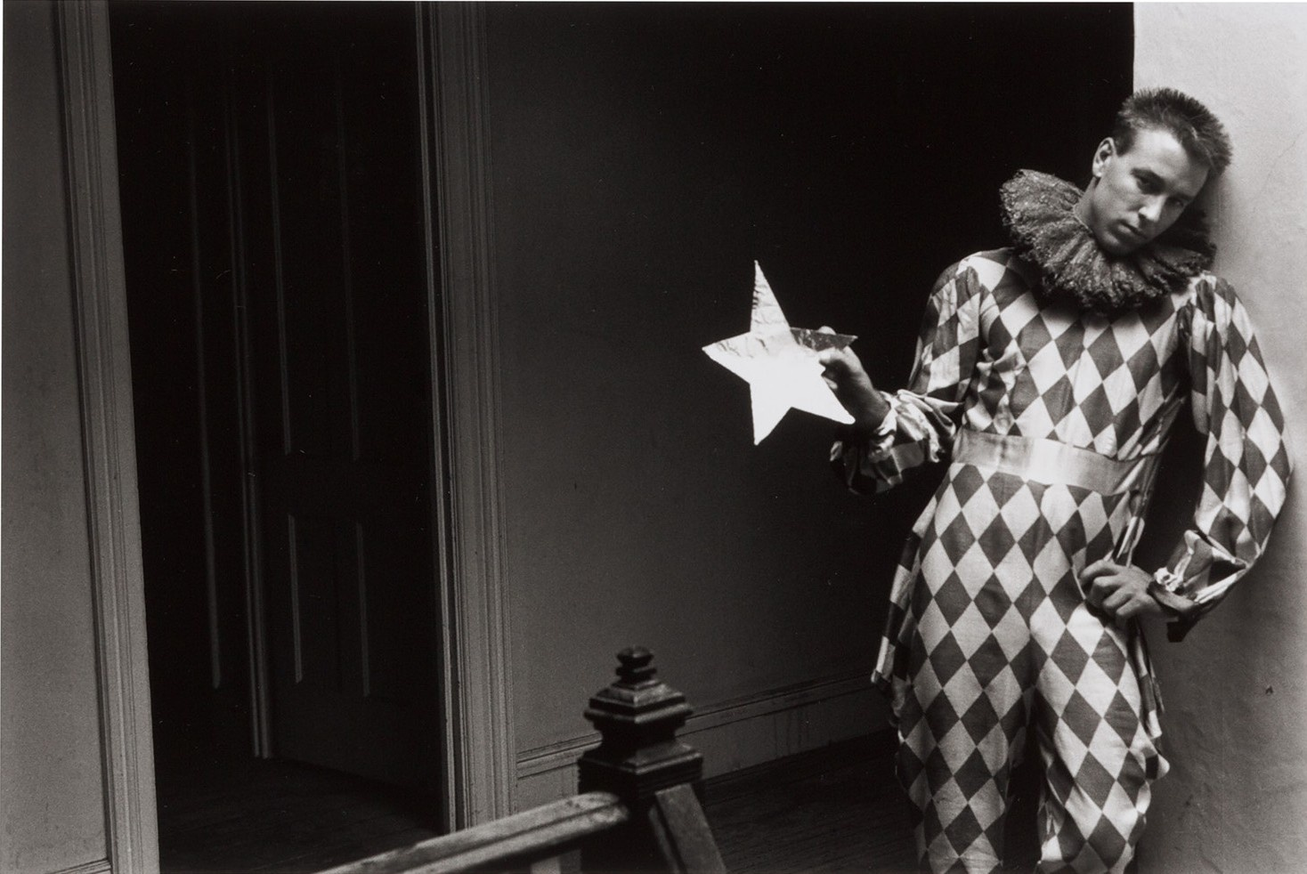 A black and white photograph of a young, light-skinned man wearing a clown costume holding a paper, gold star in a stairway.