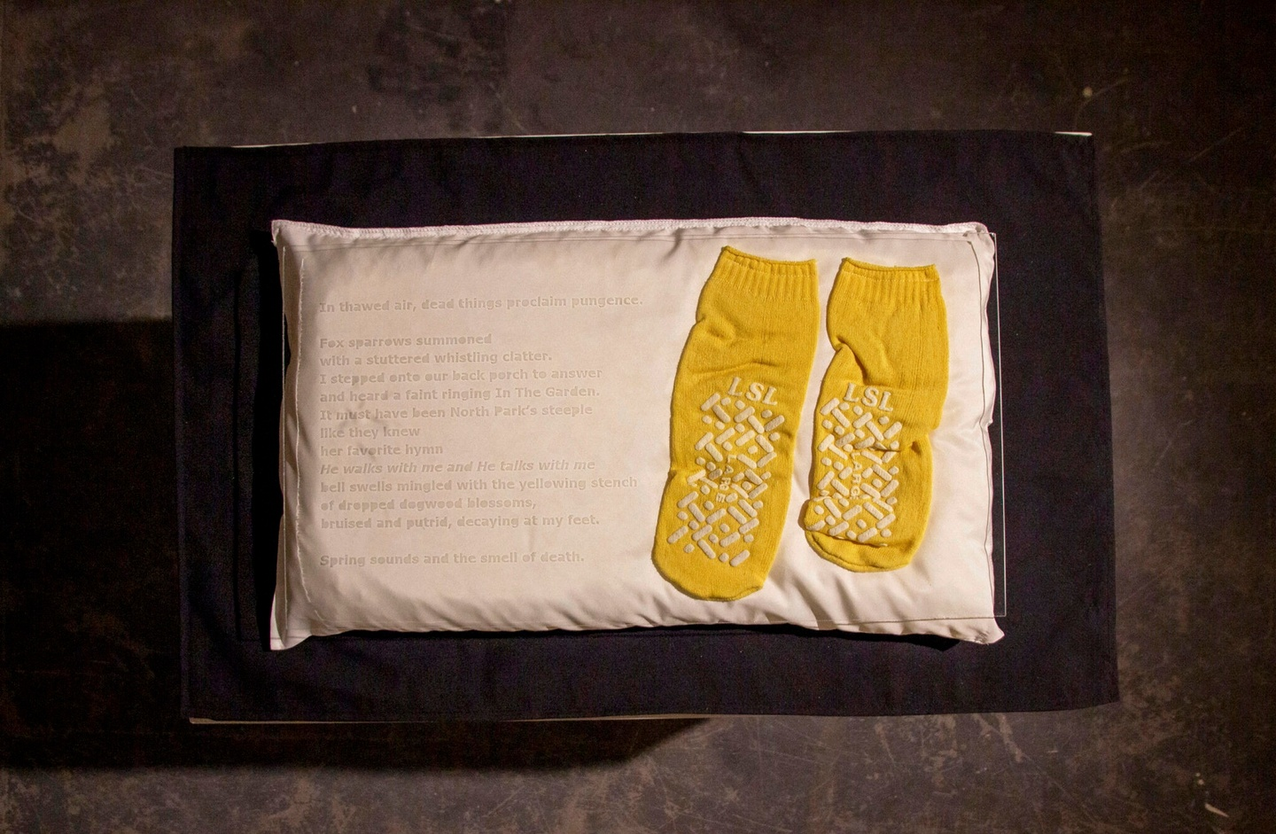 Sculpture of etched glass laid over a white pillow with writing on it and a pair of dark yellow, worn socks.