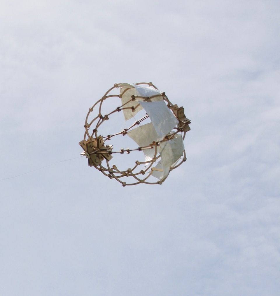 Spherical structure flying in the sky, built from thicker gold wire-like structures with connectors plus a couple of white pieces of fabric.