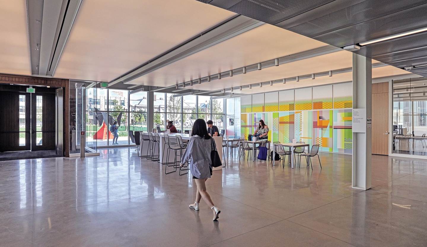 Open commons area filled with light; a bank of floor-to-ceiling windows overlooking green space and an outdoor sculpture sits next to double wooden doors. A colorful mural is on the righthand wall.