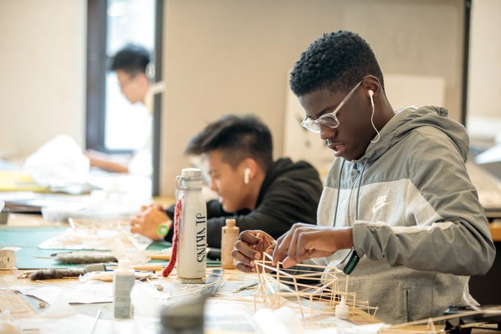 Two people sit side by side at a worktable with earbuds in working on small wooden architectural stick models.
