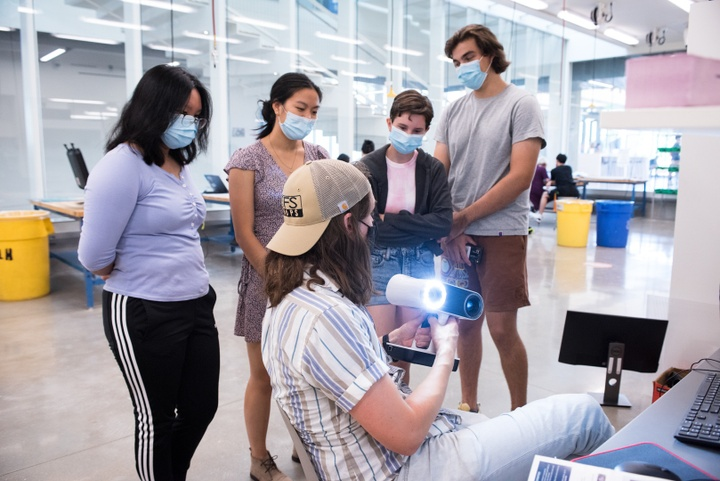 Instructor shows a group of students a lit-up handheld scanning device.